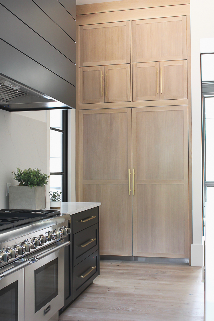 Modern kitchen with rift sawn white oak cabinet panels on built in refrigerator freezer