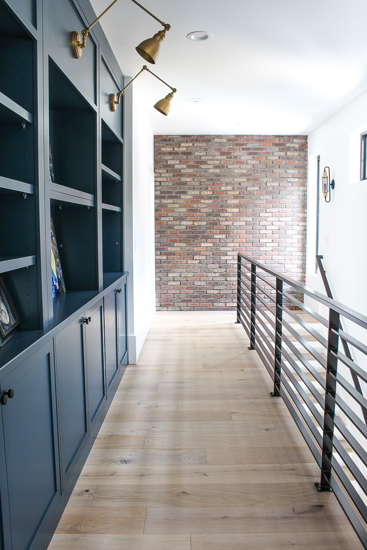 industrial brick wall, steel railing, dark blue cabinets