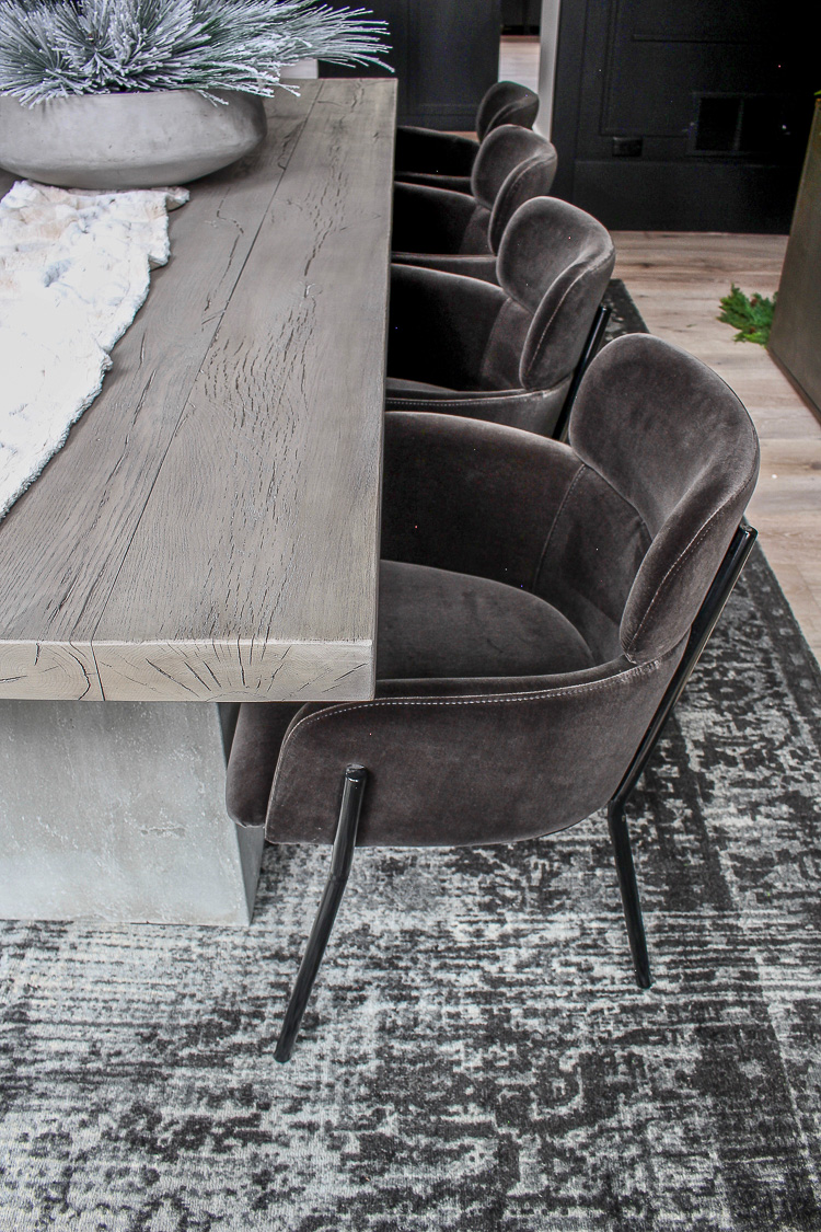 dramatic modern black dining room with aged oak and concrete table velvet dining chairs