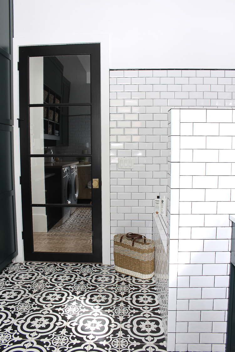 laundry room with dark green cabinets and black and white patterned tile