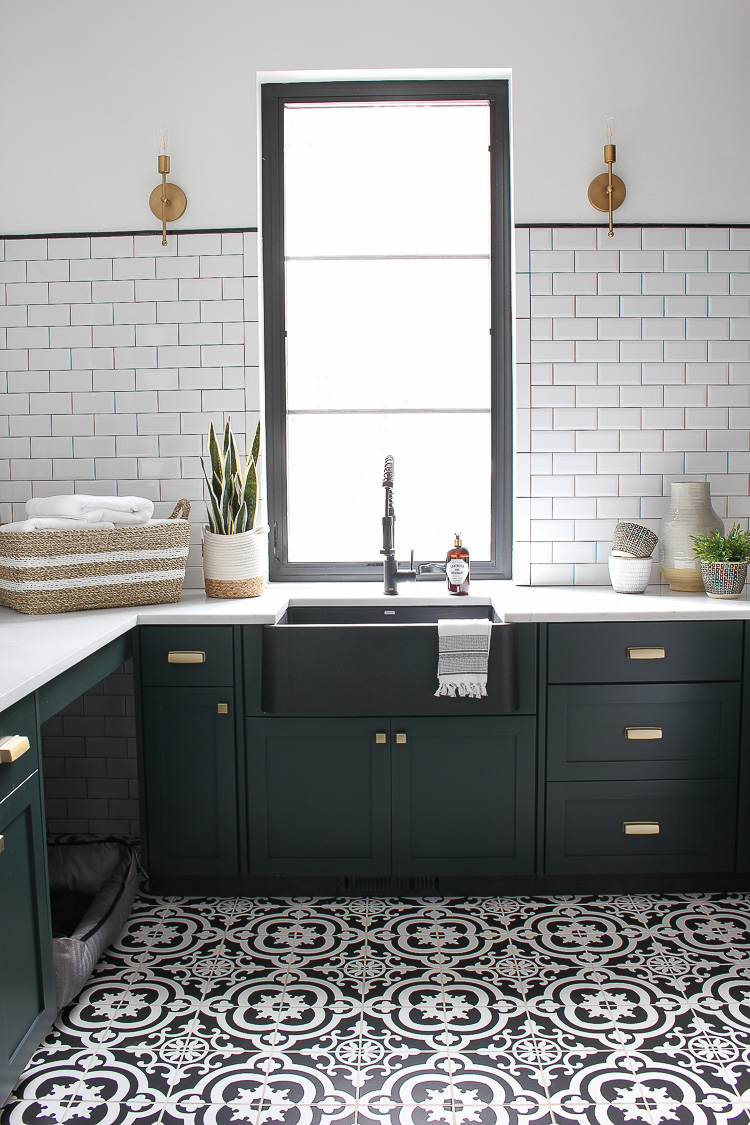 black-white-laundry-room-beveled-subway-tile-patterned-floor-dark-green-cabinets-natural-wood-gold-hardware